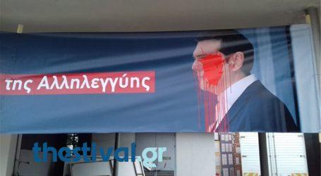 Κόκκινη μπογιά σε πανό που απεικονίζει τον Τσίπρα, λίγες ώρες πριν την ομιλία του