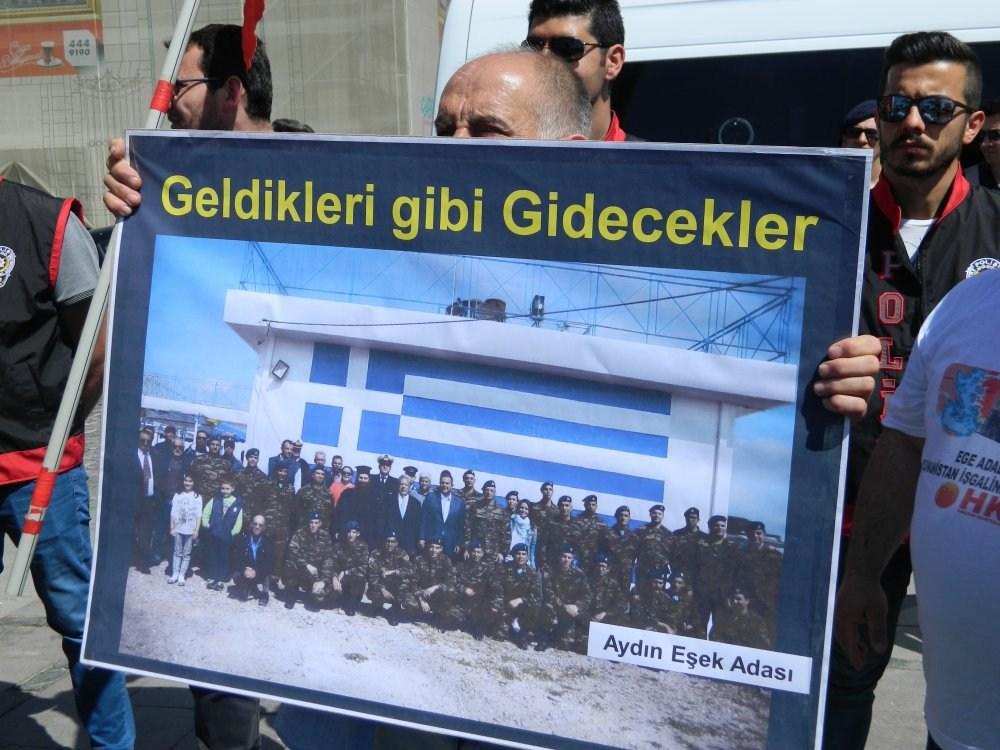 Oι διαδηλωτές κρατούσαν και μια μεγάλη φωτογραφία με κατοίκους και στρατιώτες σε κάποιο ελληνικό νησί του Αιγαίου να ποζάρουν με τον πρώην υπουργό Εθνικής Άμυνας, Πάνο Καμμένο