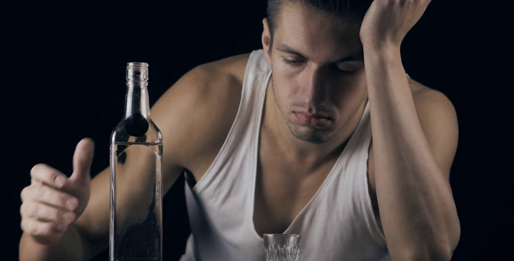 depressed man drinking vodka in a dark room bcs6hvp1l thumbnail full01