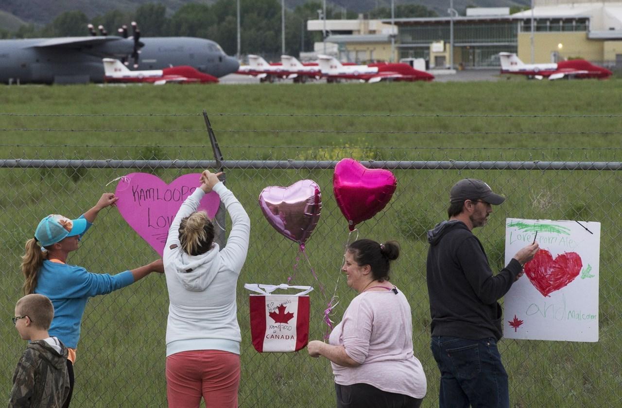 Τα αεροσκάφη Snowbirds των καναδικών δυνάμεων φαίνονται στο βάθος καθώς οι άνθρωποι τοποθετούν καρδιές και πινακίδες στο φράχτη που περιβάλλει το αεροδρόμιο στο Kamloops του Καναδά