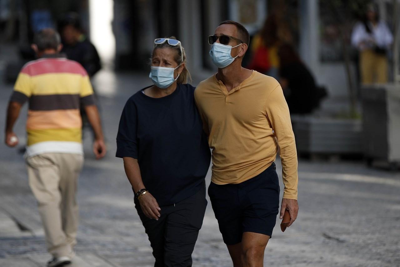 Ζευγάρι περπατά στην Ερμού, στο κέντρο της Αθήνας, φορώντας μάσκα