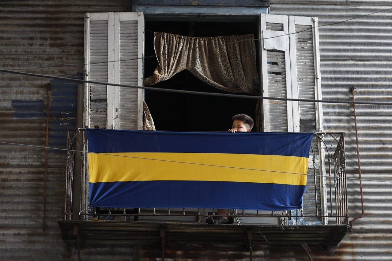 Ένα αγόρι έχει κρεμάσει στο μπαλκόνι του τη σημαία ποδοσφαίρου Boca Juniors, στη γειτονιά La Boca του Μπουένος Άιρες