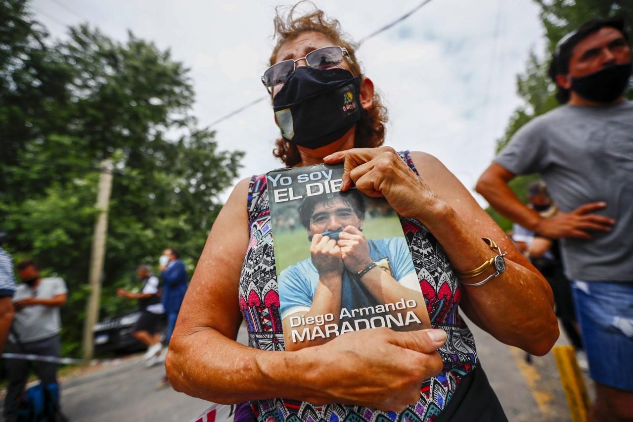 Μια γυναίκα κρατά μια βιογραφία του Ντιέγκο Μαραντόνα έξω από το σπίτι του στο Μπουένος Άιρες της Αργεντινής
