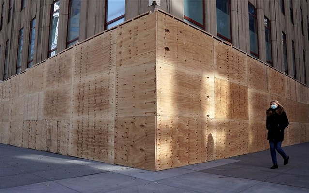 people walk past the boarded up empire state building building in anticipation of tomorrows elections