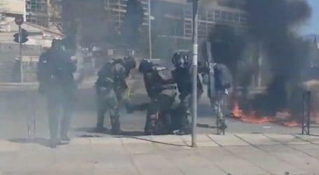 Αστυνομικοί των ΜΑΤ σβήνουν φωτιά στο πόδι διαδηλωτή που είχε ρίξει μολότοφ